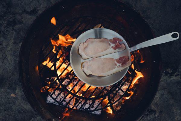 Lihaa paistumassa nuotiolla paistinpannulla.