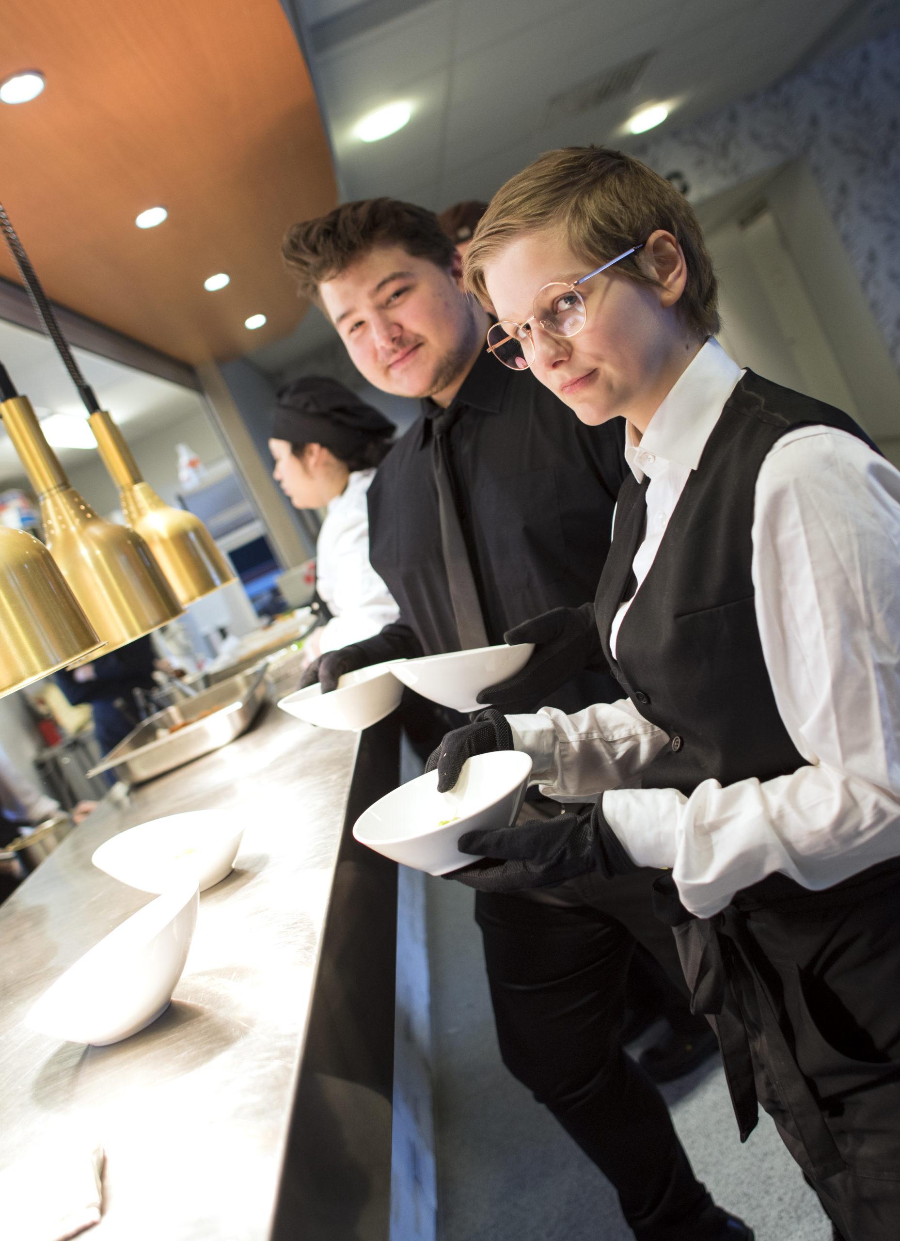 Kaksi tarjoilijaa keittiö linjaston edessä.