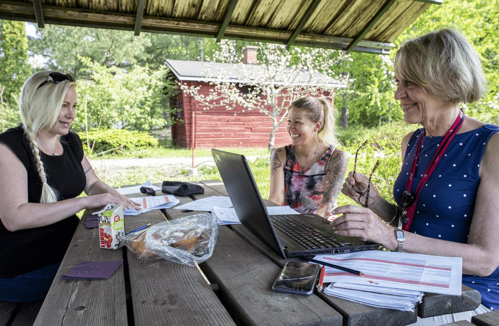 Kolme naista työskentelee pöydän ääressä.