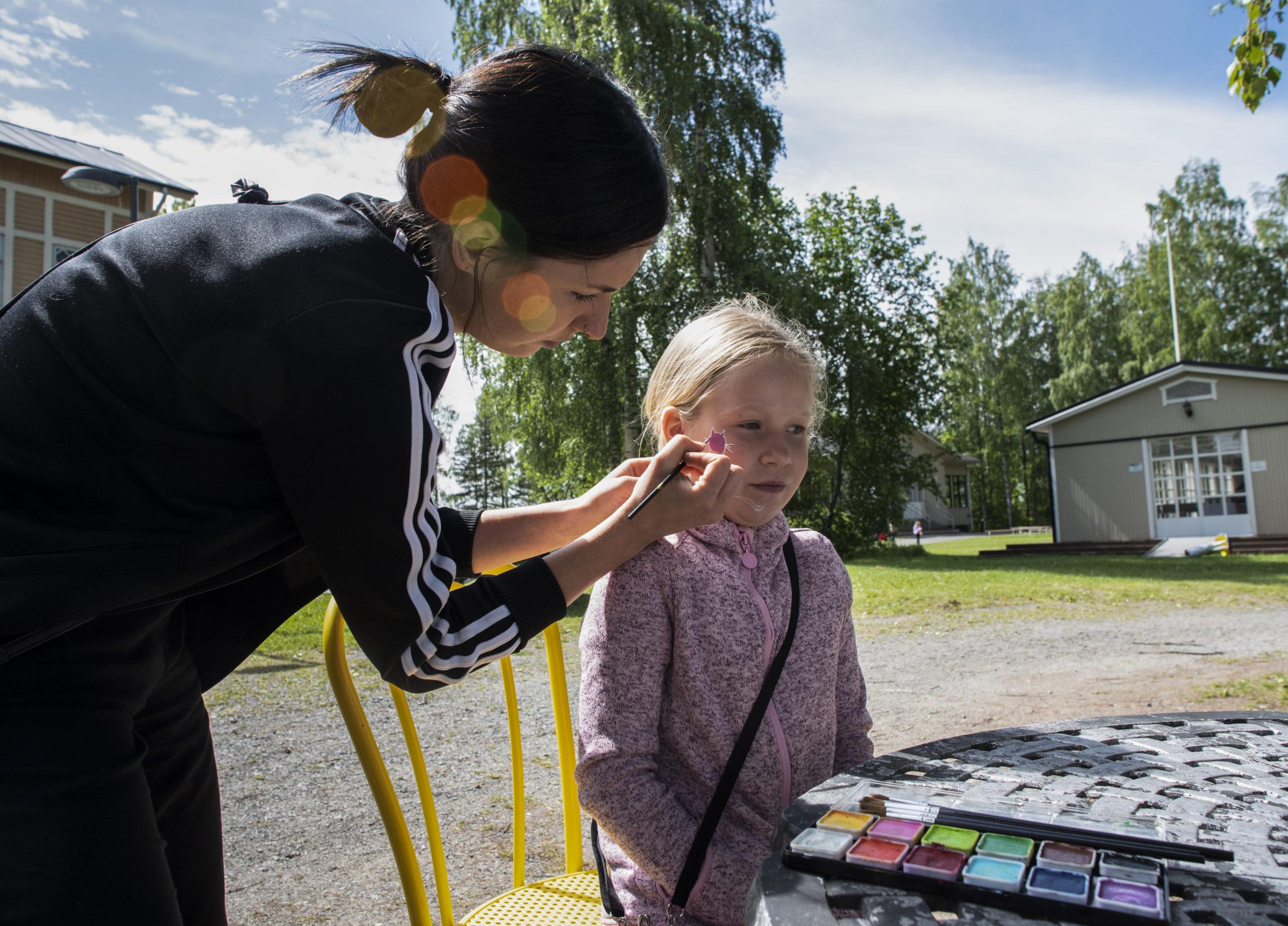 Nainen tekemässä lapselle kasvomaalausta poskeen.