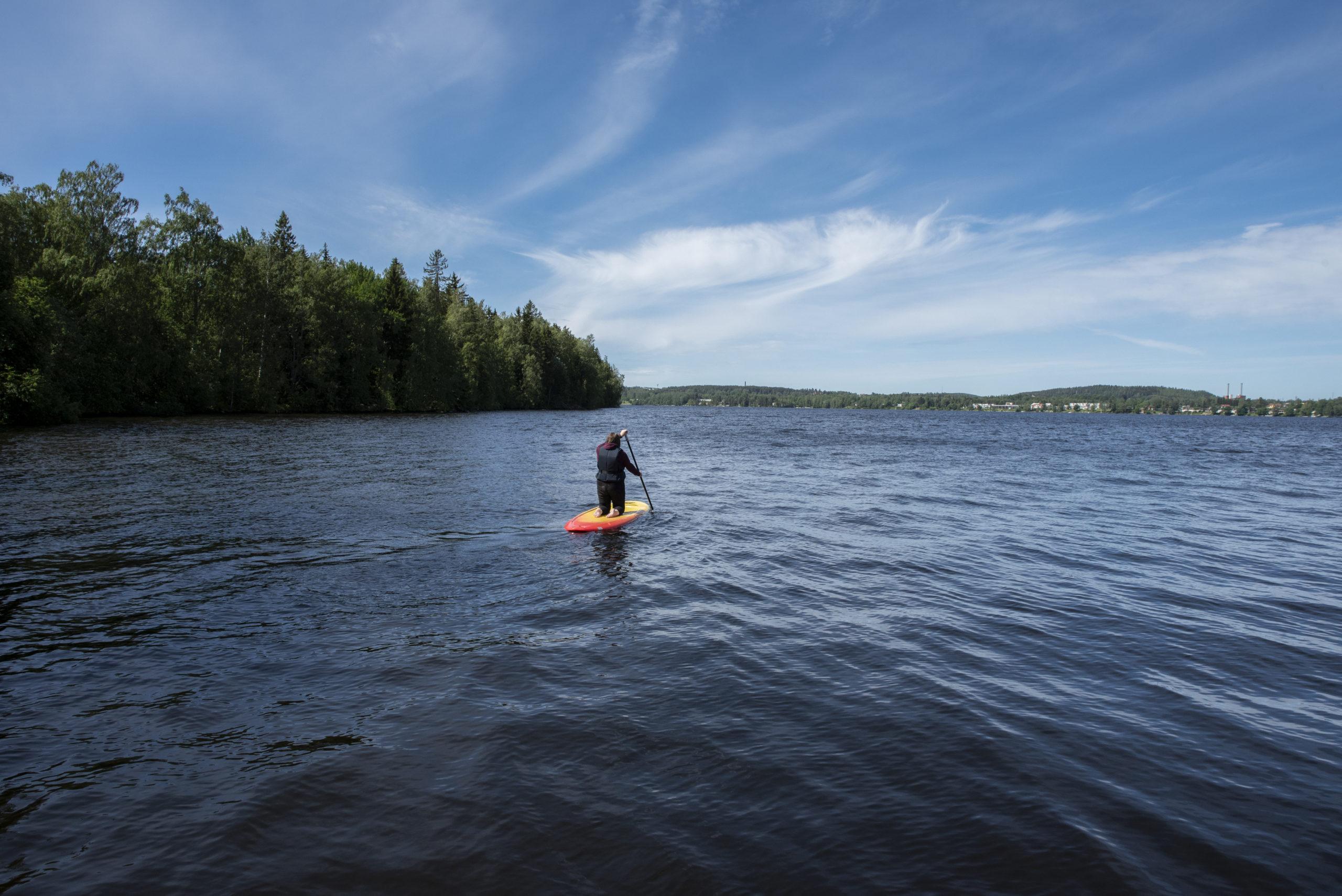 Henkilö suppailemassa järvellä.