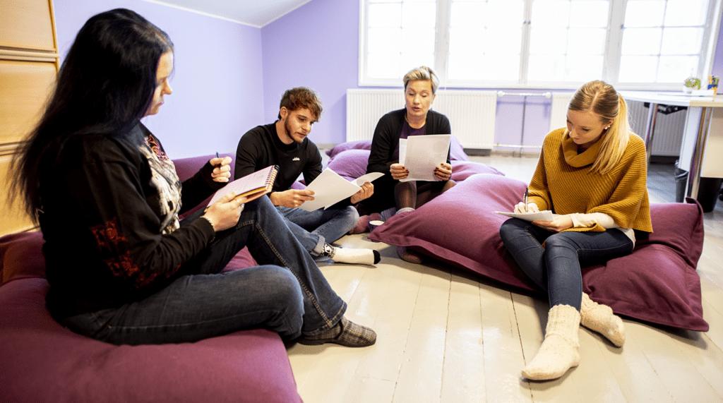Neljä henkilöä lukee ja kirjoittaa istuessaa lattitayynyillä.