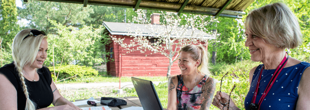 Kolme naista nauraa tietokoneen ääressä, taustalla punainen puumökki ja kukkiva omenapuu.