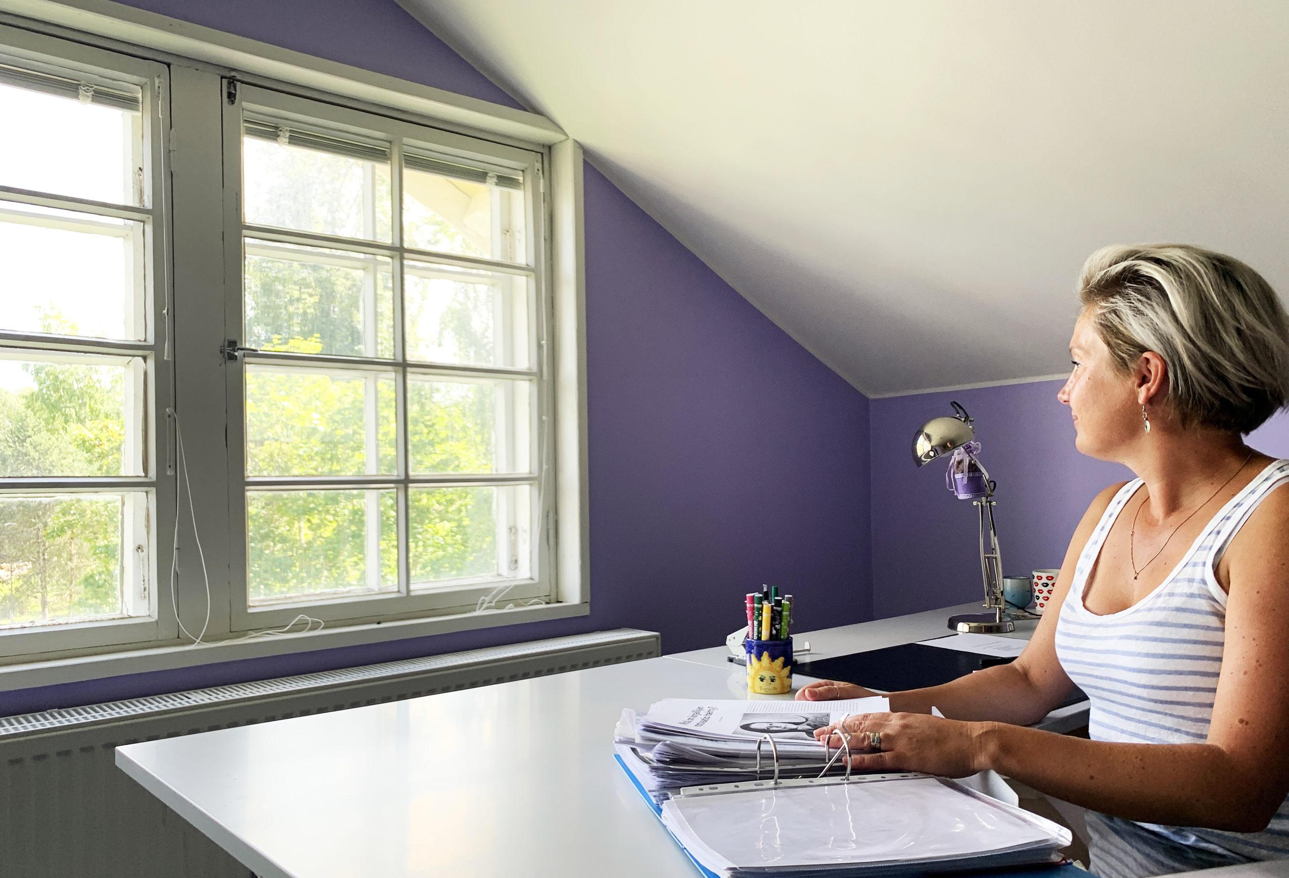 Lyhythiuksinen nainen katsoo ulos ikkunasta talossa, jossa violetit seinät.