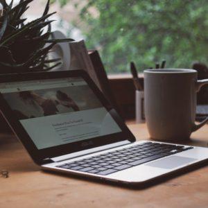 kannettava tietokone ja kahvikuppi pöydällä