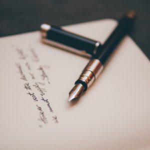 kaunokirjoitusta paperilla ja kynä