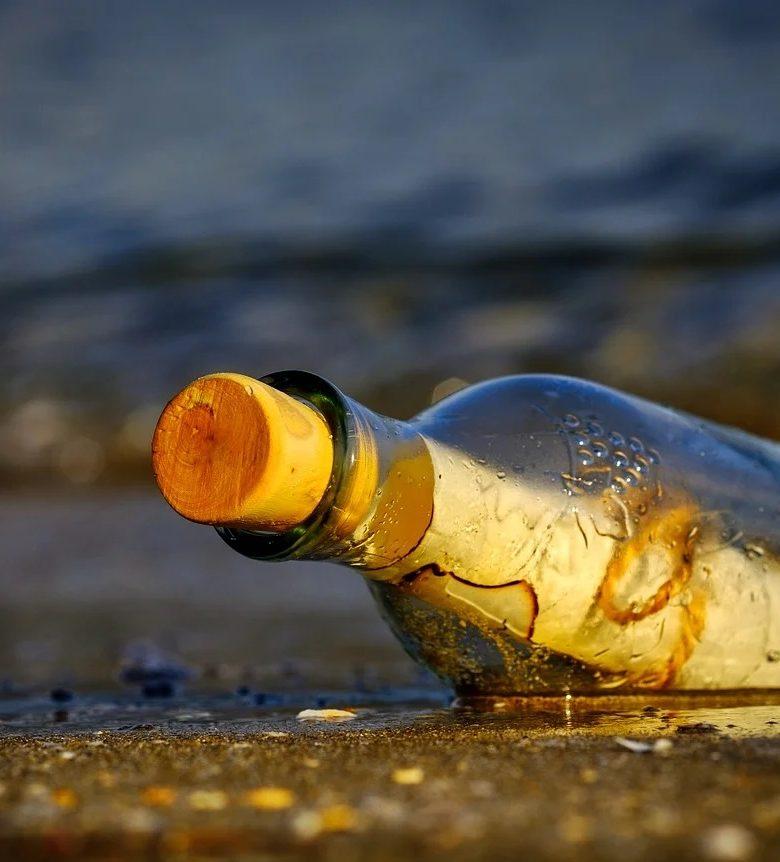 rantaan ajautunut lasipullo jossa on kirje sisällä